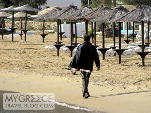 man with a fishing rod walking along Gialos beach