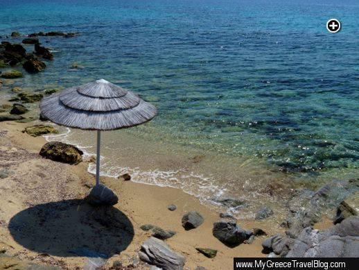 An umbrella casts its shadow on a sandy cove at Agios Ioannis beach on Mykonos
