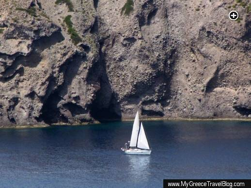 Rugged cliffs soar high above a sailboat passing the northwest coast of the Gulf of Milos