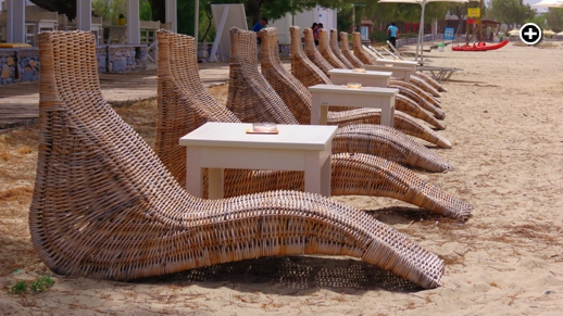 A row of contemporary wicker lounge chairs at St George's Beach on Naxos