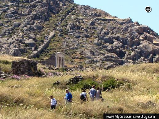 Tourists walk a path below the Temple of Isis (center left) while other Delos island visitors climb stairs to the summit of Mt Kynthos (upper left)