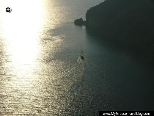A sailboat passes close to Skaros Rock during a sunset cruise at Santorini