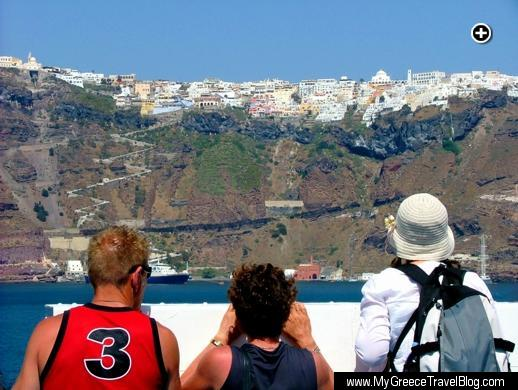 Ferry passengers look up at Fira village as their ship passes the caldera en route to the Santorini port