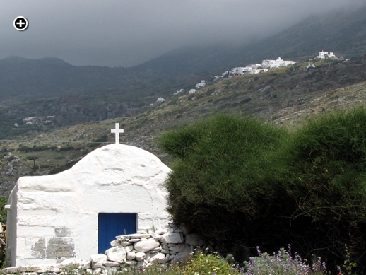 Stormclouds pass above Lagada village and a little white church on Amorgos island