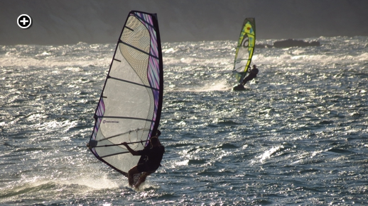 Windsurfers catch some waves and late afternoon sun on St George's Bay near Naxos Town