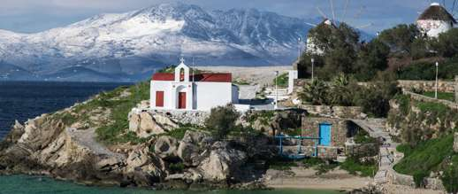 Achim Eckhardt photo of Tinos in the background behind Agios Charalampos church in Mykonos Town