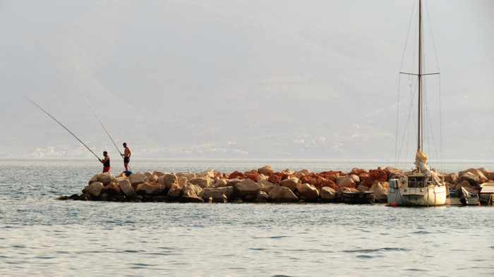 Greece, Peloponnese, Nafplio, Karathona, Karathona Bay, breakwater, jetty, fishermen, fishing,