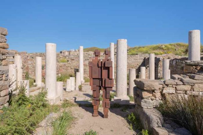 Photograph of an Antony Gormley iron sculpture displayed among the ruins on Delos island