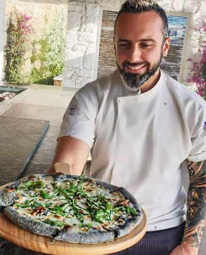 Executive chef Nikos Sotiropoulos with displays his Black Pizza creation at I Frati restaurant Mykonos