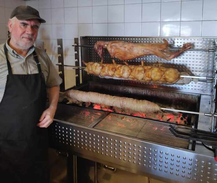 Taverna Kandavlos Facebook page photo of staff preparing rotisserie lamb chicken and pork