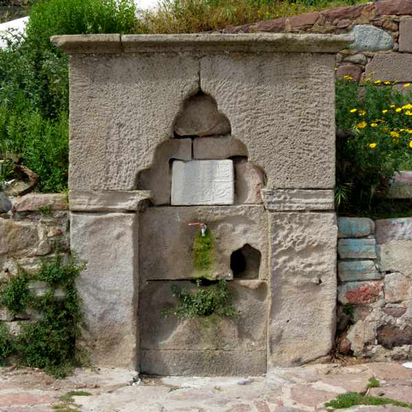 an old stone fountain at the harbour in Molyvos on Lesvos island