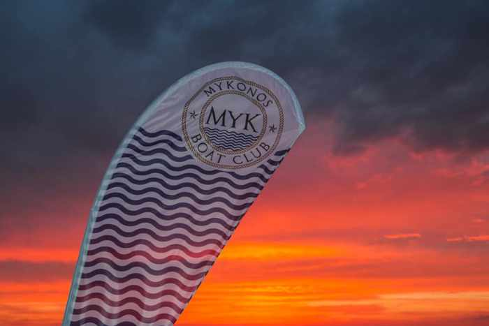 Mykonos Boat Club banner photographed at sunset